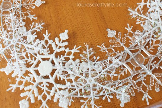 glue white tinsel snowflakes to wreath