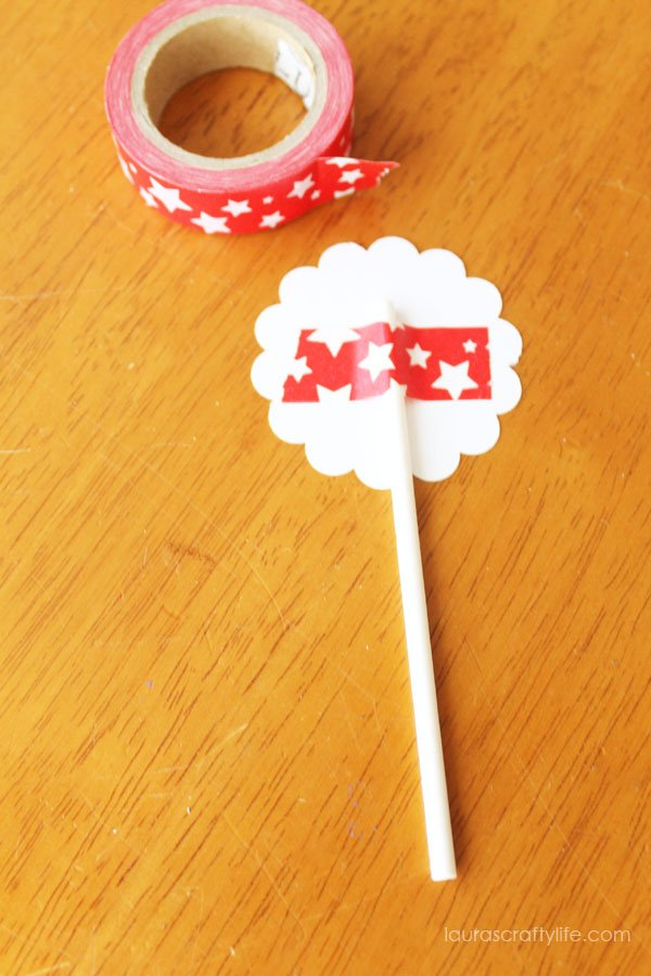 use washi tape to attach lollipop sticks to cupcake toppers