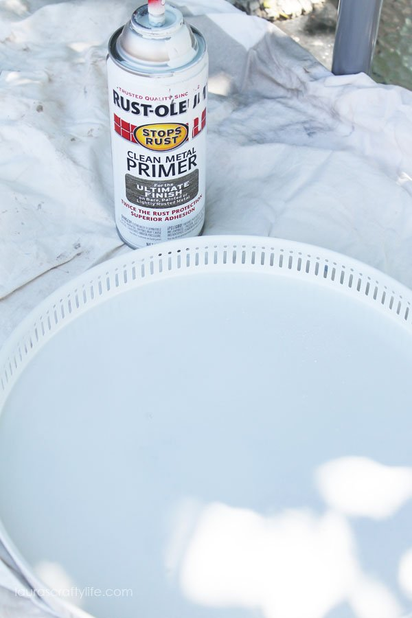Spray paint primer onto tray