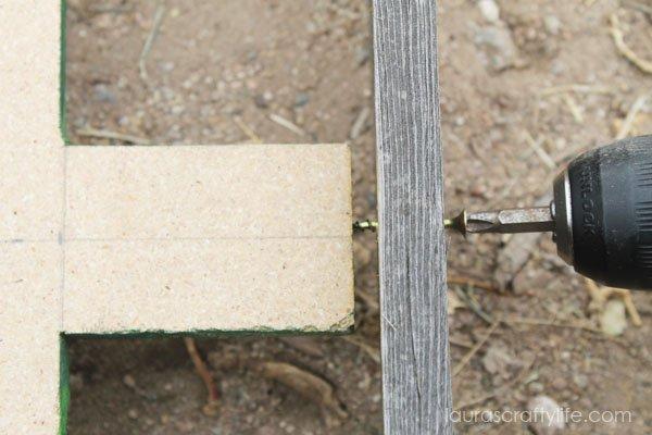 Use Ryobi drill to screw Christmas tree into fence slat