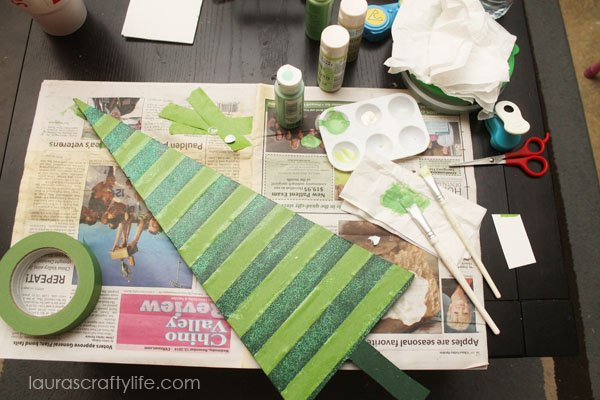 Use acrylic paint and frog tape to create patterns on Christmas trees