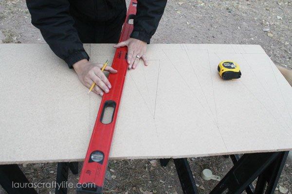 Use straight edge to draw Christmas trees onto press board