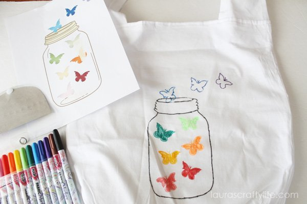 Draw on new logo with fabric markers on to tote bag