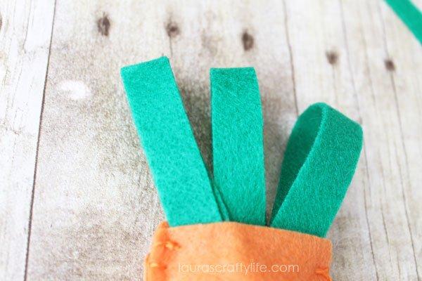 Loop the green felt and tuck inside orange felt to create leaves