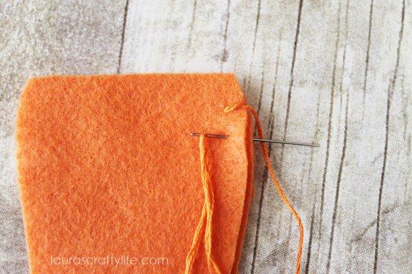 Thread needle down through felt to create a blanket stitch