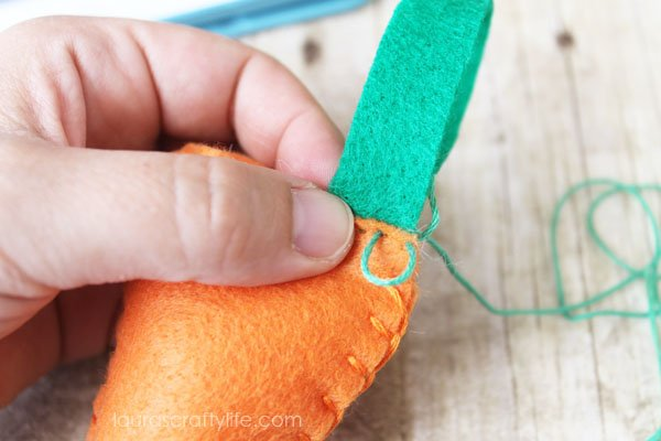 Use running stitch to attach felt leaves to the carrot