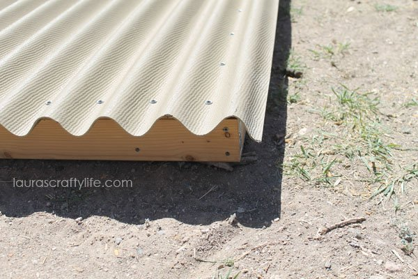 Add corrugated roofing to top of plywood frame