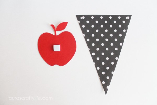 Attach apple to pennant using adhesive square