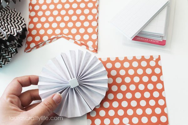 Attach accordion flowers using foam square adhesive