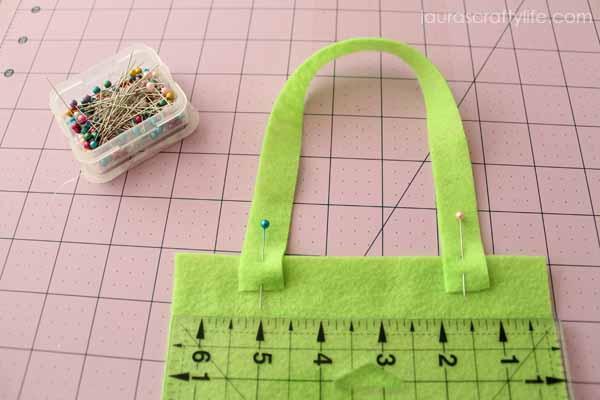 Pin straps to bag felt