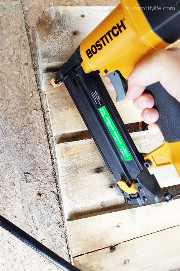 Use brad nailer to attach pallet boards to base