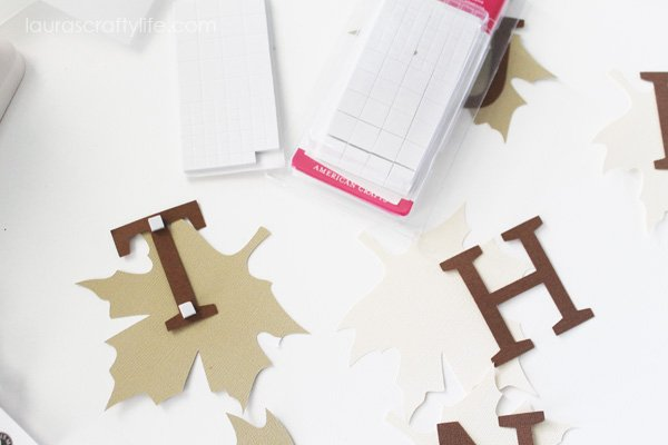 Attach letters to leaves using small adhesive squares