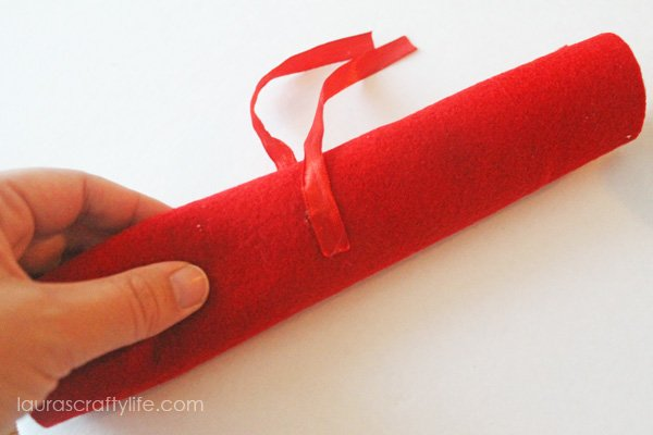 Hot glue ribbon to rolled up felt to keep everything inside secure