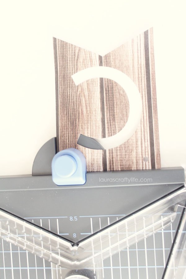 Use hole punch in banner punch board to create holes for ribbon