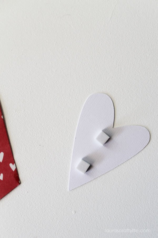 Use adhesive squares to attach heart to banner