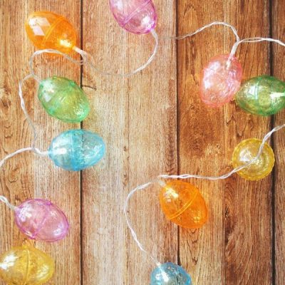 Colorful lighted Easter egg garland on wood backdrop