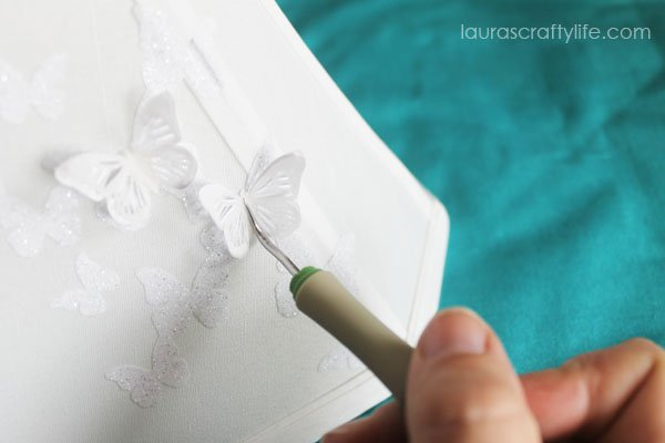 Use weeding tool to add butterflies to lampshade with hot glue