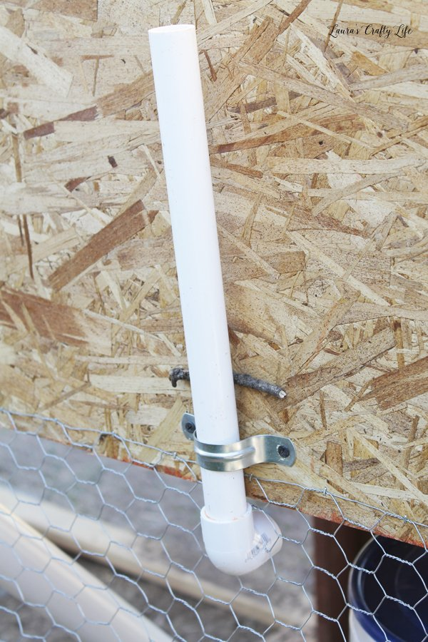 Use pipe strap to secure PVC to side of chicken coop