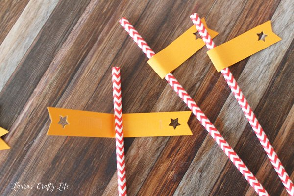 Use adhesive to attach straw flags to paper straws