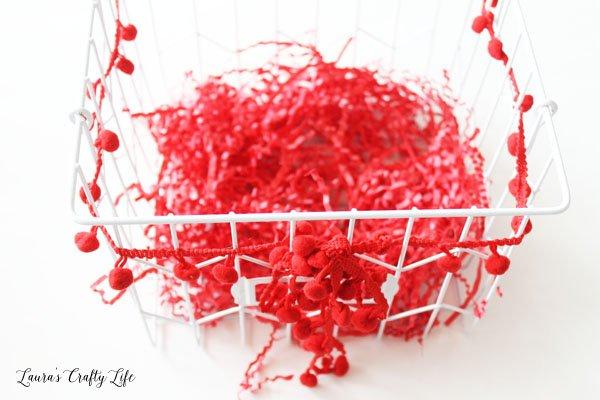 Add pom pom trim and shredded paper to basket