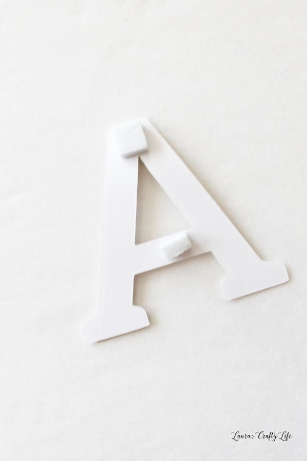 Use foam adhesive squares to attach letter