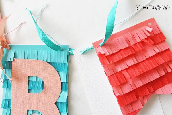 thread-twine-and-ribbon-through-top-holes-in-banner