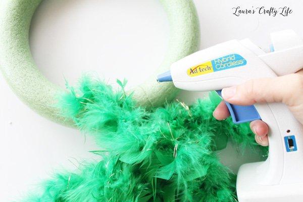 use glue gun to attach feather boa to wreath