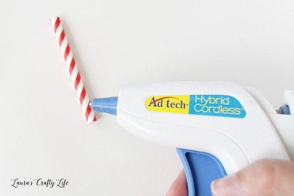 Use glue gun to attach straws to chalkboard