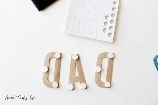 Use foam adhesive dots to attach letters to frame