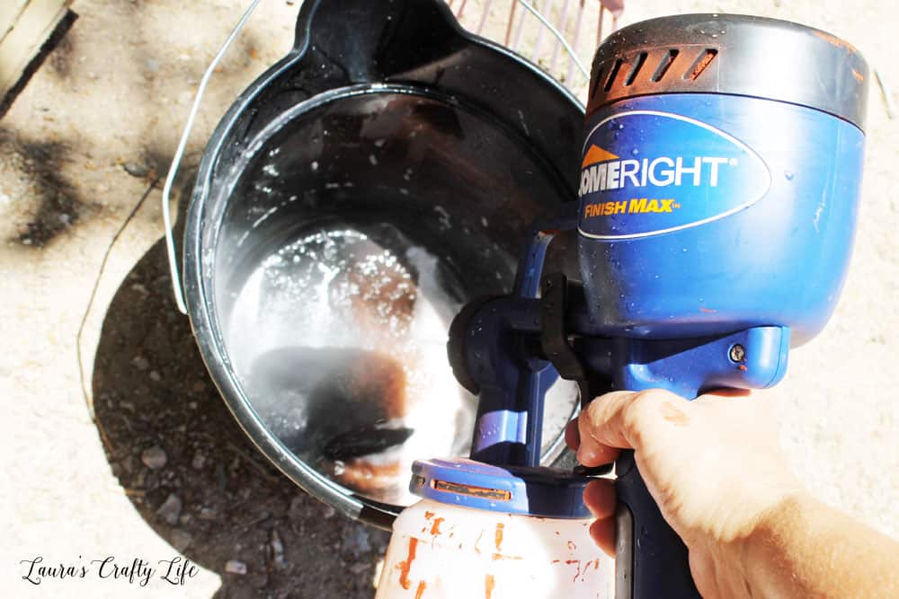 Fill HomeRight Paint Sprayer container with warm soapy water and spray