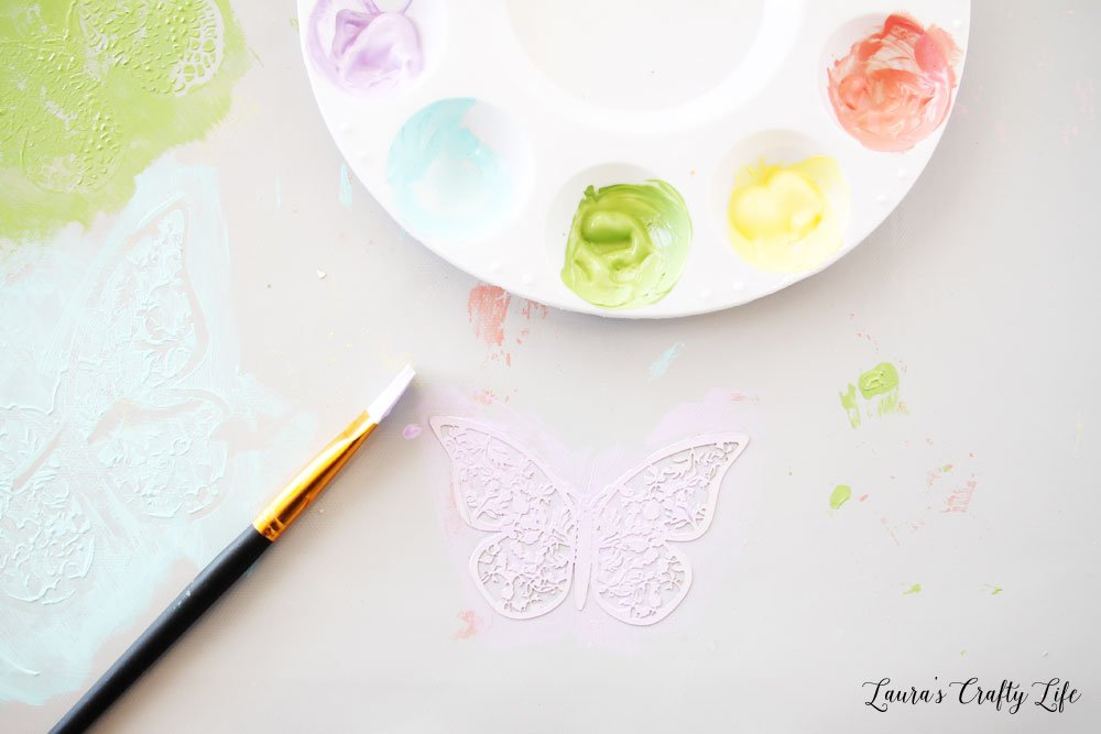 Paint each butterfly using Plaid multi-surface paint
