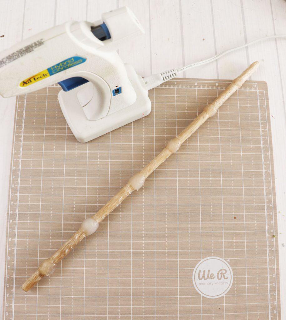 use hot glue to embellish dowel rod
